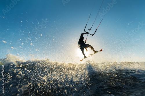 Fototapeta Surfer jumping at the sunset