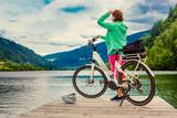 Fototapety woman with e-bike resting beside a beautiful lake-e-power 21