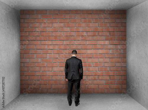 Poster Businessman with bowed head stands front of a brick wall in interior