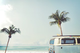 Fototapety Vintage car parked on the tropical beach (seaside) with a surfboard on the roof - Leisure trip in the summer