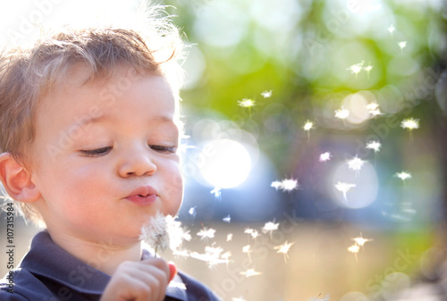 Fotografiet happy smiling child playing with dandelion outdoor in a garden