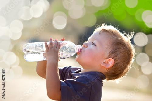 piękne blond dziecko pić wodę na zewnątrz