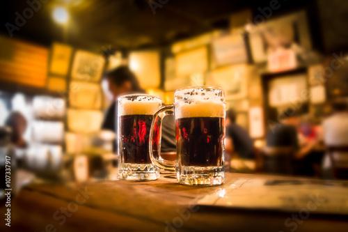 Defocused bar blur with 2 mugs of beer in focus Poster