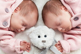 Newborn twins sisters sleeping with a teddy bear in the middle.