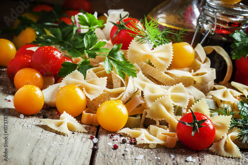 Italian food: Assorted dry pasta, herbs, garlic, red and yellow Poster