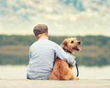Fototapety mein bester Freund, Junge sitzt mit seinem Hund am Steg