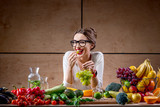 Fototapety Young and cute woman eating grapes at the table full of fruits and vegetables in the wooden interior. Healthy food concept. Beauty and wellbeing