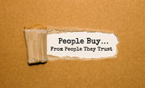The text People buy from people they trust appearing behind torn brown paper