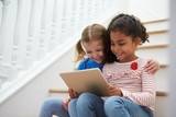 Two Girls Sitting On Staircase Using Digital Tablet