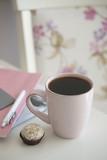 Напиток в розовой кружке и маленький десерт