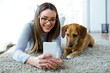 Beautiful young woman with her dog using mobile phone at home.