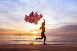 happiness concept, psychology of happy people, young woman running with multicolored balloons on the beach - 107478114