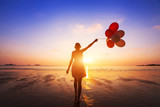 happiness concept, positive emotions, happy girl with multicolored balloons enjoying summer beach at sunset - 107479343