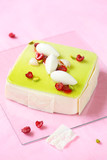 Square  Pistachio Raspberry Mousse Cake with Lychees on a light pink background.