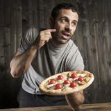 Uomo con i capelli scuri con la pizza in mano su sfondo legno scuro gusta la pizza - sfondo legno