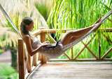 Young woman lying in a hammock with laptop - 107530799