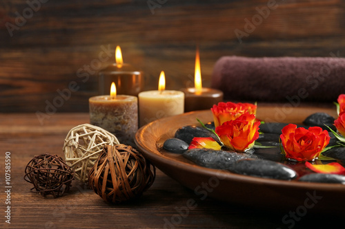 Spa wooden bowl with water, flowers and stones on wooden background