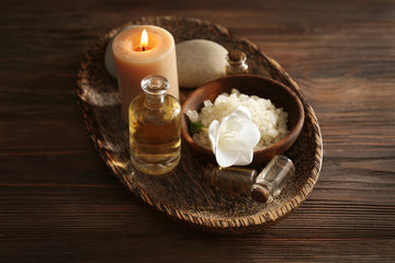 Spa set with sea salt, exotic flowers and candles on wicker tray © Africa Studio