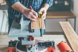Carpenter measure wooden board in his workshop.
