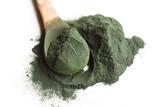 Spirulina algae powder on wooden spoon isolated on white