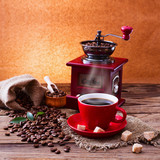 Fototapety Coffee cup and saucer, coffee grinder, coffee beans in sack and spilled on wooden table.