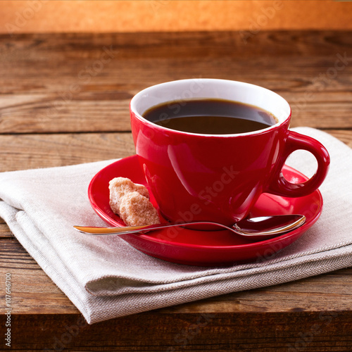 Aluminium Koffiebonen Coffee cup and saucer on tablecloth on wooden table. Dark background. Coffee concept. Selective focus.