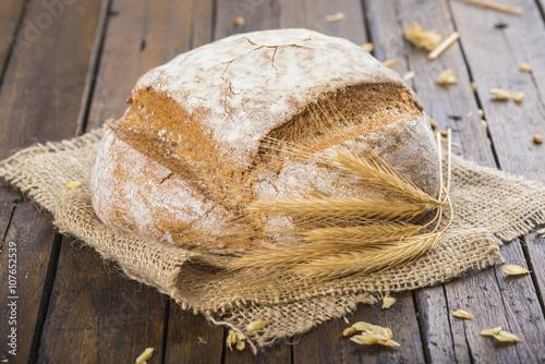 obraz PCV Hogaza de pan de trigo y centeno sobre una arpillera en la mesa de la cocina decorada con espigas de cereales