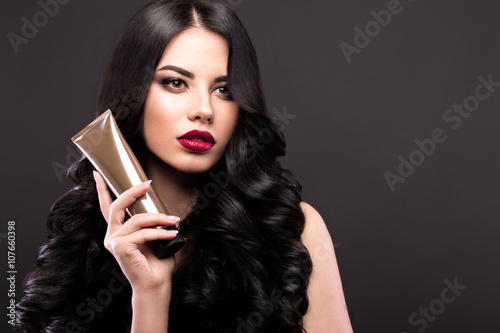 Tela Beautiful brunette model: curls, classic makeup and red lips with a bottle of hair products