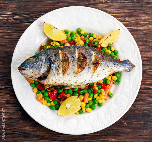 Фото: Sea bream baked with herbs and lemon, vegetable mix.