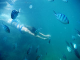 Underwater shot of the woman moving on the breath hold in the depth