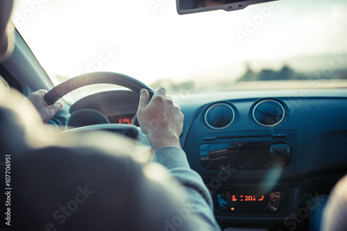 Man driving car, hand on steering wheel, looking at the road ahead. - 107706951