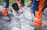 Construction worker cutting concrete paving stabs or metal for s