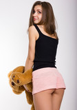 leggy blonde girl in pink shorts and a short tank top holding a teddy bear