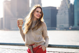 Fototapety Beautiful woman holding paper coffee cup and enjoying the walk in the city