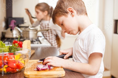 Small boy cooking together with his sister Poster