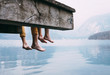 Father and son swung their legs from the wooden pier on mountain