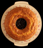 Round ciambellone cake on a ceramic plate. In the middle a bowl with coulis of mixed berries. Background: total black.