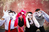 Four mimes looking through binoculars on a red wall.