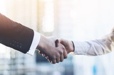 Closeup image of business partners making handshake outdoors, modern office or skyscrapers on the background, flare light - 107883597