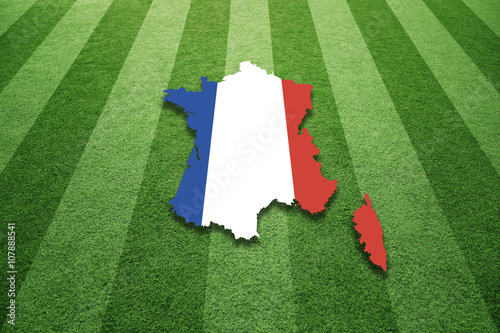 Sunny socccer artificial green grass field with France map in flag colors background.