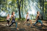 Group of  young people keep in shape exercising in forest