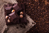 Fototapety Roasted coffee beans, chocolate and nuts on the wooden background