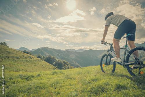 Młody sportowy mężczyzna jazdy rower w słonecznym dniu w górze