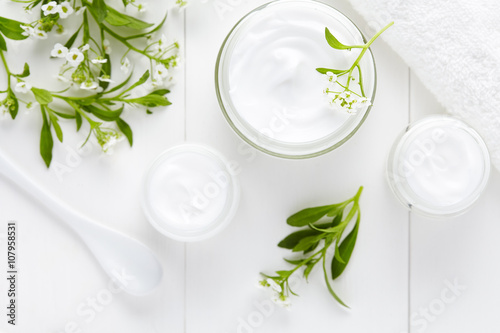 Medical therapy cosmetic cream with herbal flowers hygienic skincare product wellness and relaxation mask in glass jar on white background