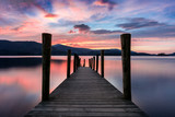 Stunning vibrant pink and purple sunset on a beautiful evening at Ashness Jetty, Derwentwater, Lake District, UK.