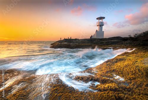 Fototapeta Lighthouse through the air to the sea at night.