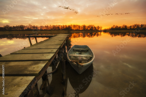 Poster Łódka zacumowana przy drewnianym pomoście w piękny poranek