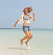 beautiful happy girl jumping on the beach