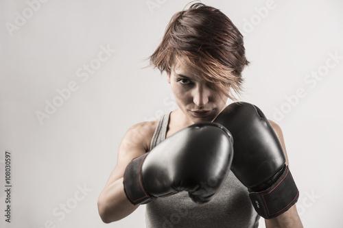 Póster donna boxer sta per sferrare un pugno con i suoi guantoni neri