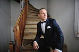 Elegant young fashion groom sitting at old spiral wooden stairs